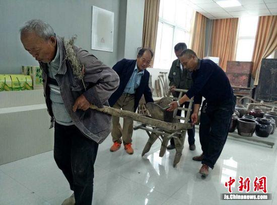 在官路小区村史馆,几位老人一起演示农具使用,回味以往幸福的艰苦生活。