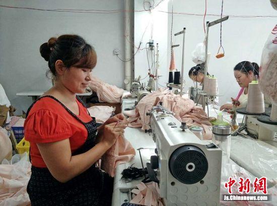 张婷和村里姐妹们一样就近在社区服装厂工作,不用抛家到外地受苦。