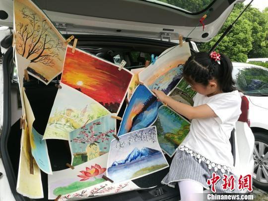 8岁的秦孙言之正在整理自己的画作,准备贩售出去。 钟升 摄