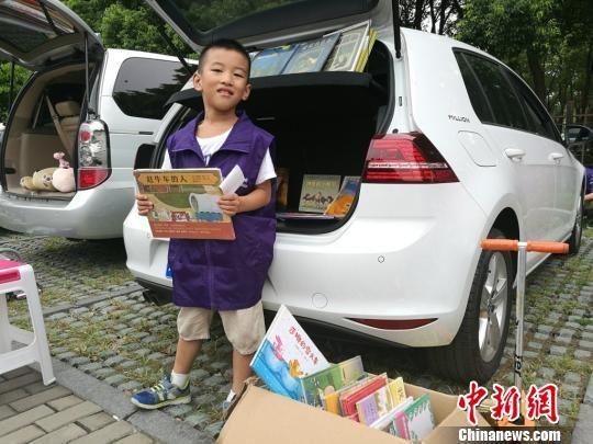 7岁的胡修齐在卖自己幼儿园时的小人书,半小时就卖出了8本。 钟升 摄