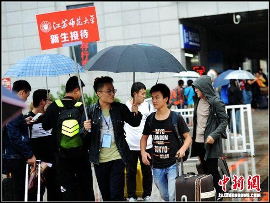 """徐州十几所高等院校新生接待处的学长们在出站口为学弟学妹撑起人生的""""雨伞""""。"""