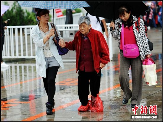 两位孝顺的子女搀着老人小心地走在雨中。