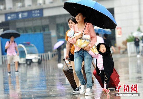 怀里抱一个,手里拉一个,这位年轻的妈妈雨中张望着远处的车辆。