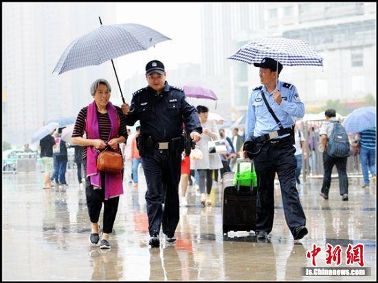 两位执勤警察为老年旅客打着雨伞拉着行李,帮助办理进站事宜。