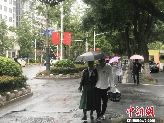 11日,南京街头迎来降温降雨,市民纷纷撑起雨伞。 杨颜慈 摄