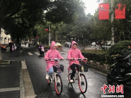 11日,南京迎来降温降雨。图为市民披上雨衣出行。 杨颜慈 摄