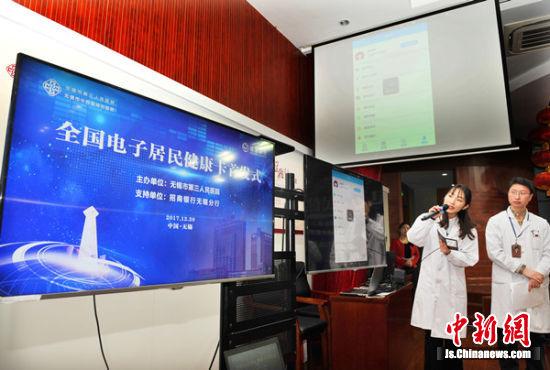 图为工作人员介绍三院电子健康卡。