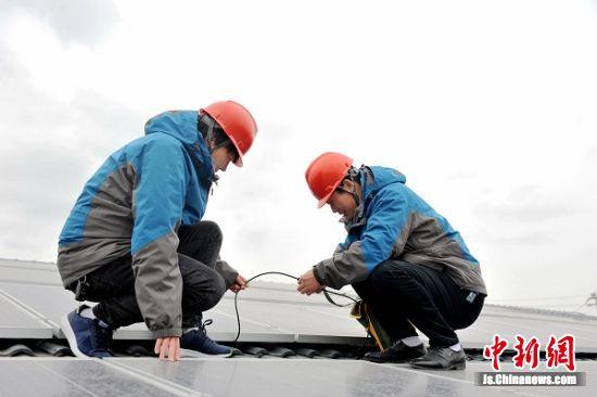 1月3日,国网滨海县供电公司大套供电所员工于广生、江泉来该镇扶贫光伏电站为其安装表计并检查设备。