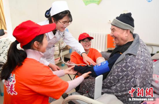 为老人们测量血压。桂宝林 冯耀 摄