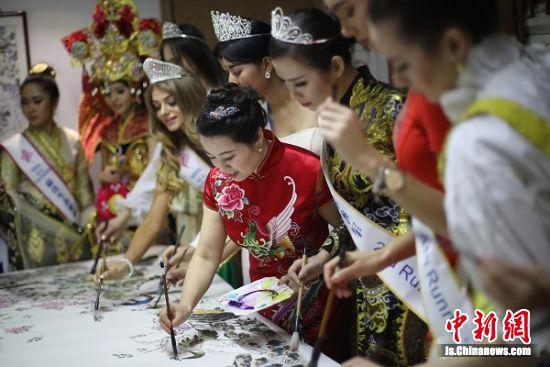 佳丽们与著名艺术家王丽萍联手创作《凤舞骄阳》中国画作品。 泱波 摄