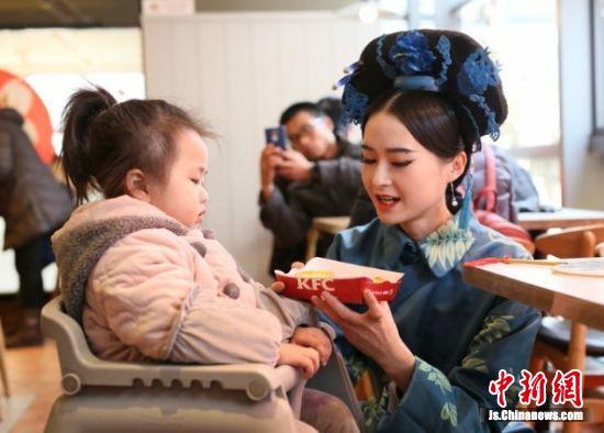 图为身穿古装的美女与用餐孩童互动。