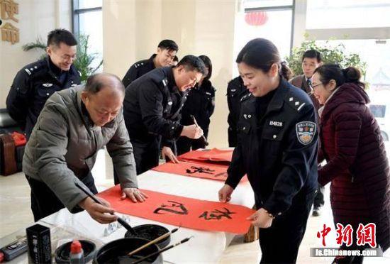 徐州市公安局老干部书画协会代表现场挥毫泼墨,写春联。田永春摄