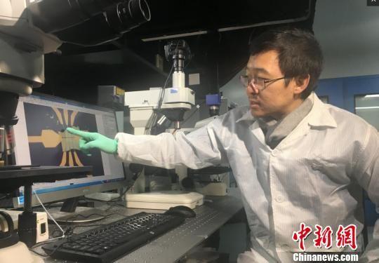南京大学教授缪峰向记者介绍这种新结构电子元件的抗热原理。 申冉 摄