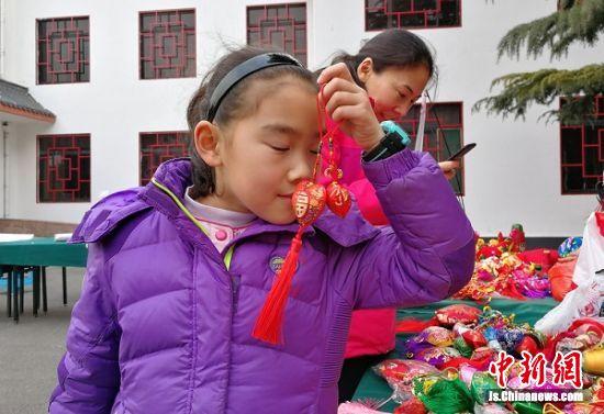 从徐州城里来游玩的小学生为精美的香包所陶醉。