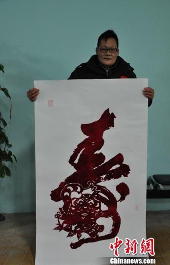 """邢浩南展示创作的巨幅十二生肖""""寿""""作品。 张景良 摄"""