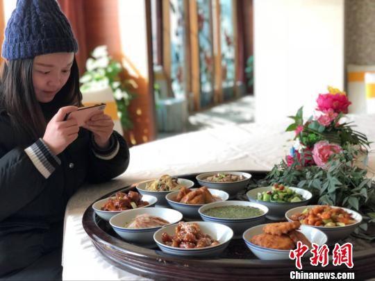 """一位美女在拍摄""""老南京""""年夜饭怀旧""""十大碗""""。 朱晓颖 摄"""