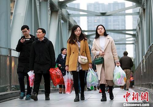 资料图:两位成都市民提着购买的年货。 中新社记者 王磊 摄