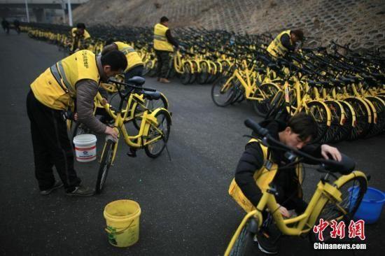 """资料图:工作人员为共享单车集体""""洗澡""""。 中新社记者 佟郁 摄"""