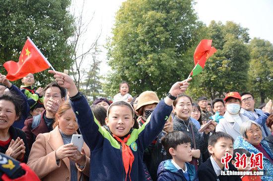 戴着红领巾的小学生挥动手中的国旗为选手加油。朱志庚摄
