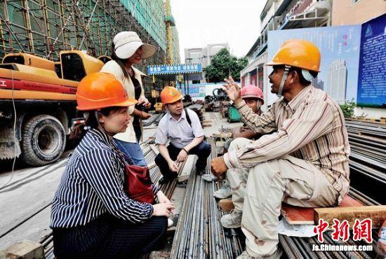 服务组成员在柬埔寨建设工地上与当地员工交流。王广祥 摄