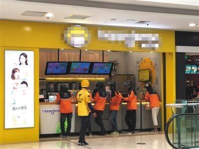 4月12日,一家饮品店门前等待取外卖的滴滴外卖骑手与路过的美团外卖骑手。B04-B05版摄影/新京报记者 陈维城