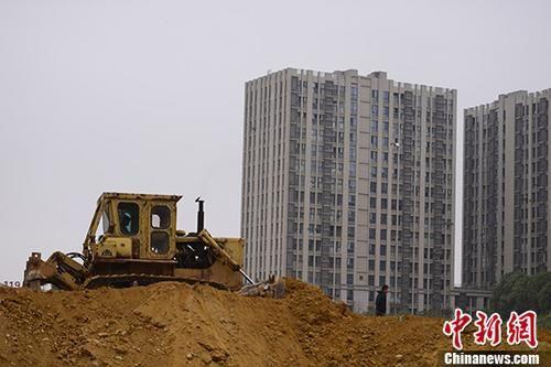 资料图:一楼盘土地上,推土机正在作业。 中新社记者 杨华峰 摄