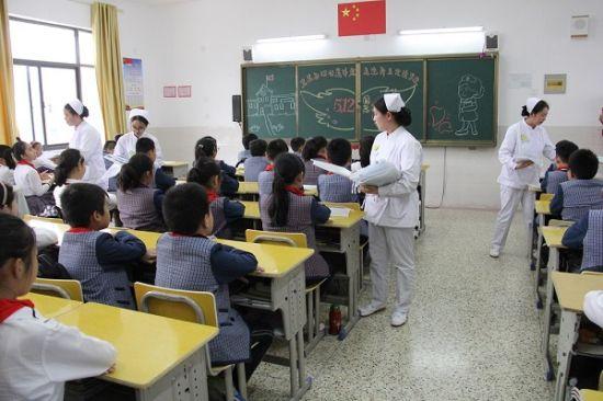 图为护士向学生赠送学习用品。