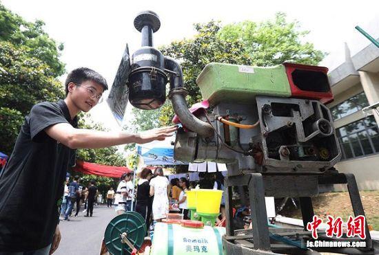 大学生被展出的农耕机械吸引。 中新社记者 泱波 摄