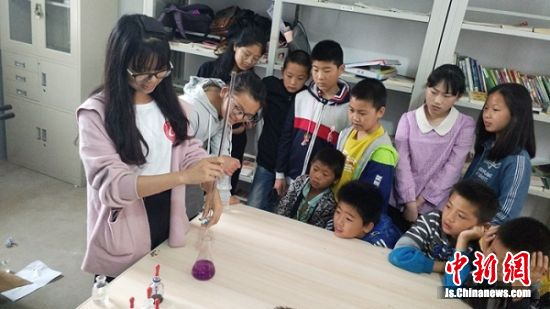 大学生志愿者和孩子们做化学试验。