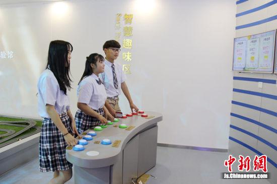 指导卫校学生参与体验馆内趣味答题活动。魏守凤摄