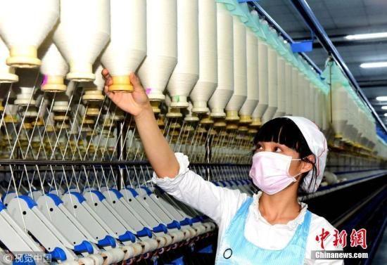 资料图:澳门永利官网线上娱乐纺织工人正在生产纱线。周晓明 摄 图片来源:视觉中国