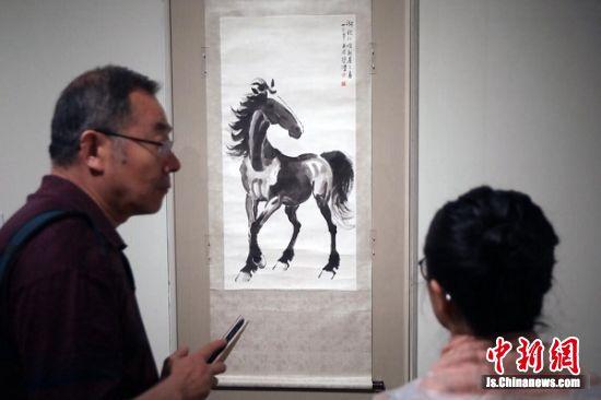 观众被徐悲鸿的画作《马》吸引。 泱波 摄