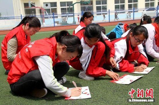 志愿者与留守儿童书写心愿卡、互赠礼物。