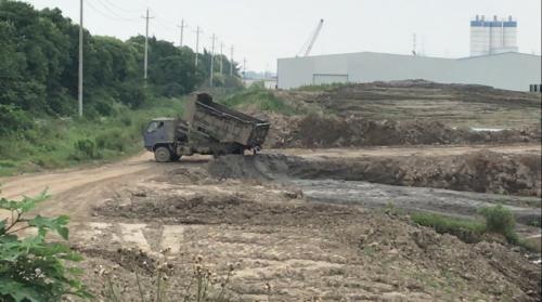 督察人员检查时,一辆翻斗车开来倾倒泥浆。图片来源:生态环境部网站。