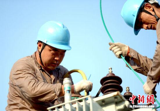 盐城供电公司盐都营业部兴达农服公司员工在连接配电变压器接线。