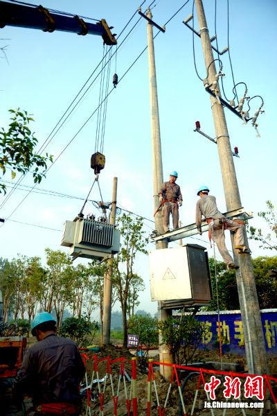 盐城供电公司盐都营业部兴达农服公司员工在吊装10千伏乔李线大李1号配电变压器。