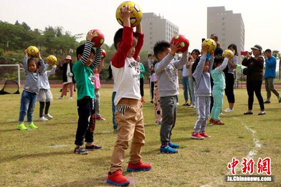 幼儿园小朋友在跳足球操。