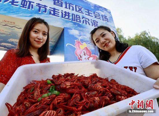 图为当地龙虾餐饮店工作人员展示刚出锅的盱眙龙虾。