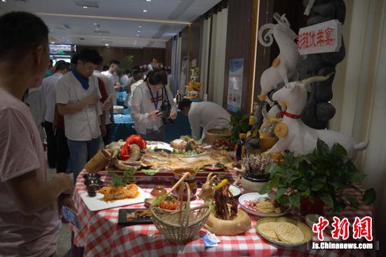 游客对着满桌的全羊宴拍照记录。
