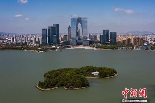 """1994年2月,中国和新加坡政府签署《关于合作开发建设苏州工业园区的协议》,苏州工业园区""""呱呱坠地""""。 经过多年的发展,截至2017年,园区已实现地区生产总值2350亿元人民币,每平方公里土地GDP达8.6亿元人民币。牛津大学、哈佛大学,微软、苹果、西门子等世界知名高校、企业也纷纷将分支机构、研究院所落户在园区。图为航拍苏州工业园区核心商务区。(7月20日拍摄) 中新社记者 泱波 摄"""