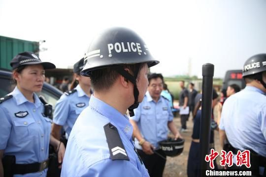 """图为冒着酷热高温,执行法院围堵""""老赖""""。扬州市中级人民法院供图"""