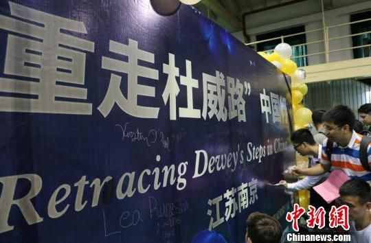 参与者们在活动背景板上签名。 泱波 摄