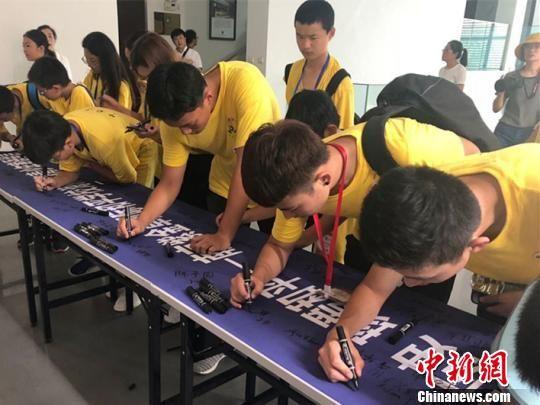 图为营员在和平寄语横幅上签名。 杨颜慈 摄