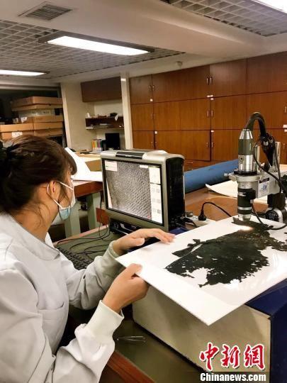 文物专家在修复这批珍贵的丝织品文物。资料图