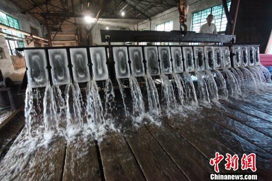 工人将生产好的冰块倾倒出模具 孟德龙 摄