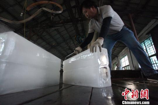 工人正在搬运冰块。 孟德龙 摄