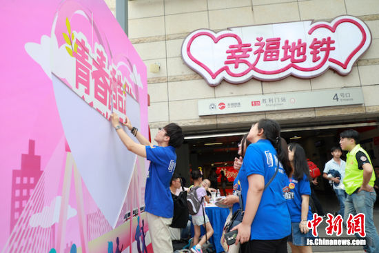 图为志愿者们在张贴青春标记。