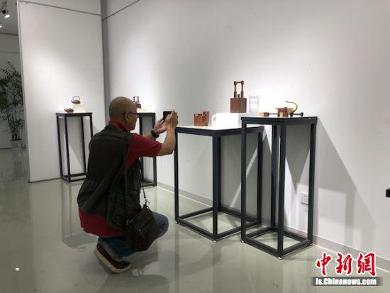 观展嘉宾拿出手机拍摄这些展出的作品。