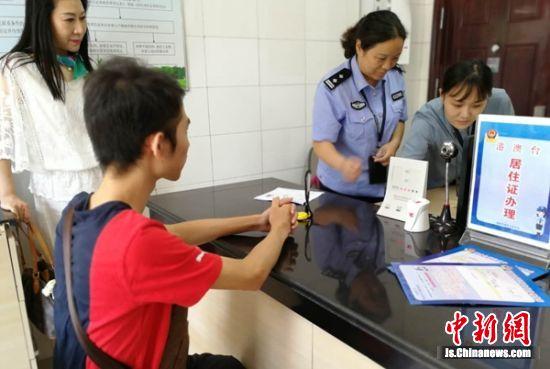 第一个领取港澳居民居住证的陈文旭在办证大厅等待指纹检验。