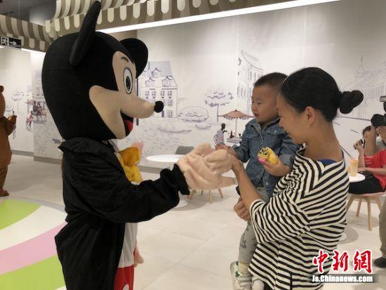 卡通人偶与往来旅客互动。